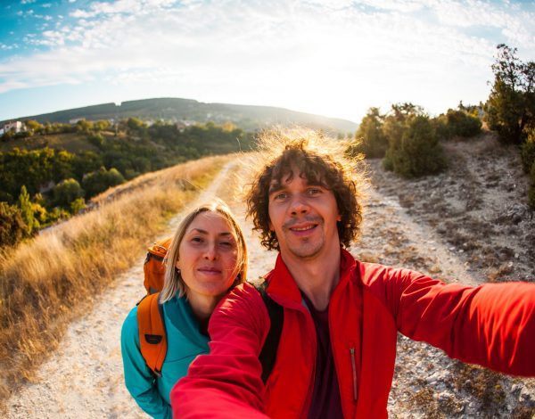 The man and the girl are traveling with backpacks. Selfie on a smartphone. Friends walk in picturesque places. A couple is photographed against a beautiful nature.